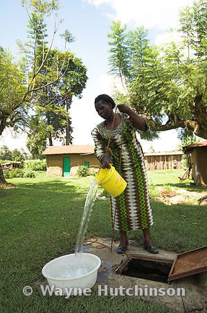 African woman in brightly coloured costume taking clear water from village well and emptying into bucket Kenya Africa
