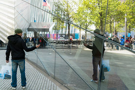 A tourist takes a picture of himself in the reflection of 9/11 Memorial Museum near World Trade Center, New York City.
