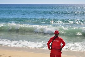 Lifeguard watches swimmer in waves