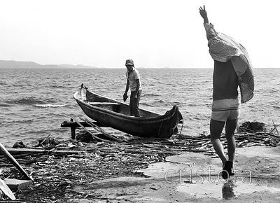 fishermen prepare to set out in a dugout canoe