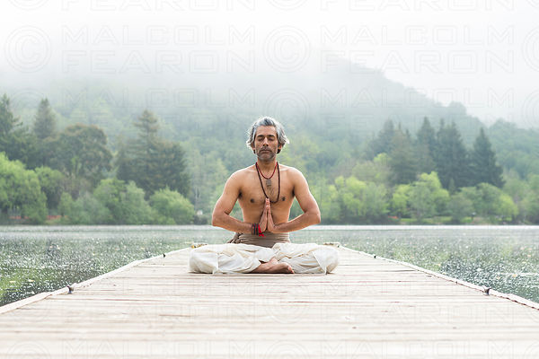 solo man in lotus position yoga pose on wooden dock