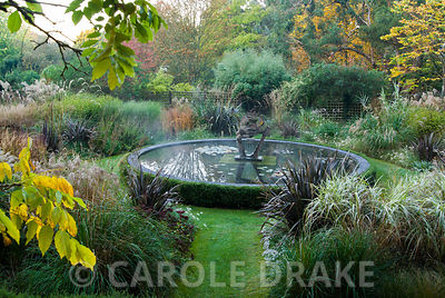 Dragon Garden with beds full of grasses including tall miscanthus, Calamagrostis 'Karl Foerster' and Phormium tenax atropurpurea edged with Pennisetum villosum. Central circular pond features dragon sculplture. Knoll Gardens, nr Wimborne, Dorset, UK