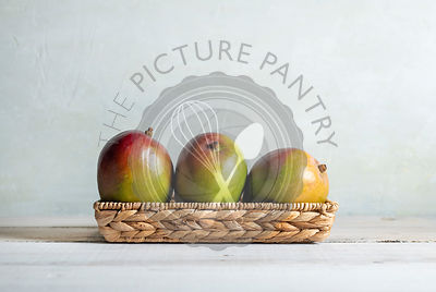 3 colorful mangoes in a basket set on a white wood surface with bright, sunny, natural light.