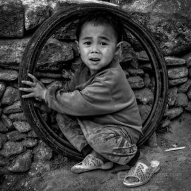Small Black Hmong Boy Playing with Tyre