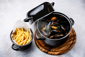 Shellfish Mussels Clams in black cooking dish pan and French Fries