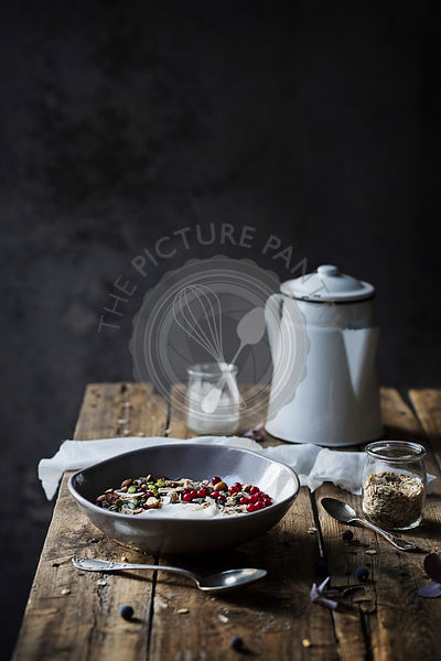 Breakfast on wooden table: yogurt with oat flakes, seeds, pistachios, hazelnuts and currants