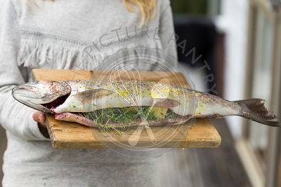 Girl Holding Whole Stuffed Rainbow Trout.