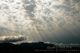 Crepuscular rays (God Beams) shining through broken cloud over silhouetted mountain