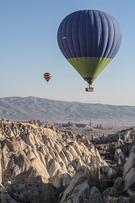 Hot air balloons above eroded limestone ravine, Cappadocia, Turkey, March 2006.