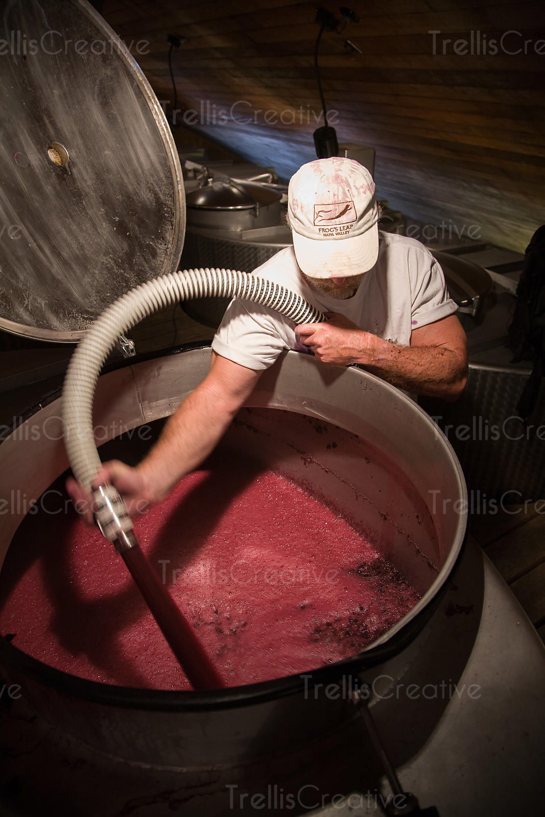 A cellar worker pumps over red wine in a large tank