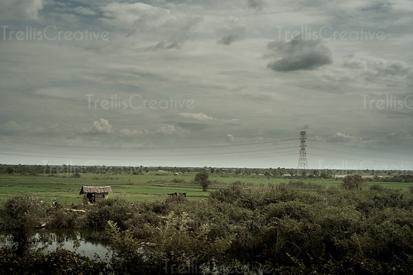 A rice farmer's hut sits under looming storm clouds in the Cambodian countryside