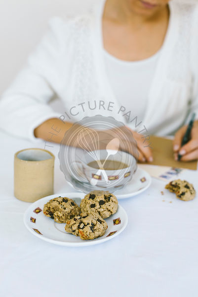A woman writing a letter while having oatmal cookies and coffee.