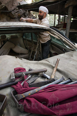 A Sikh man repairs cars in Delhi, India, with the tools of his trade in the foreground