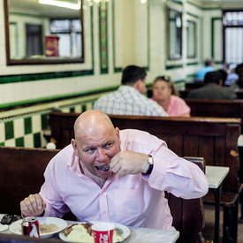 A man eats a lunch of pie, mash and jellied eels in Manze's Eel, Pie and Mash shop on Tower Bridge Road, London