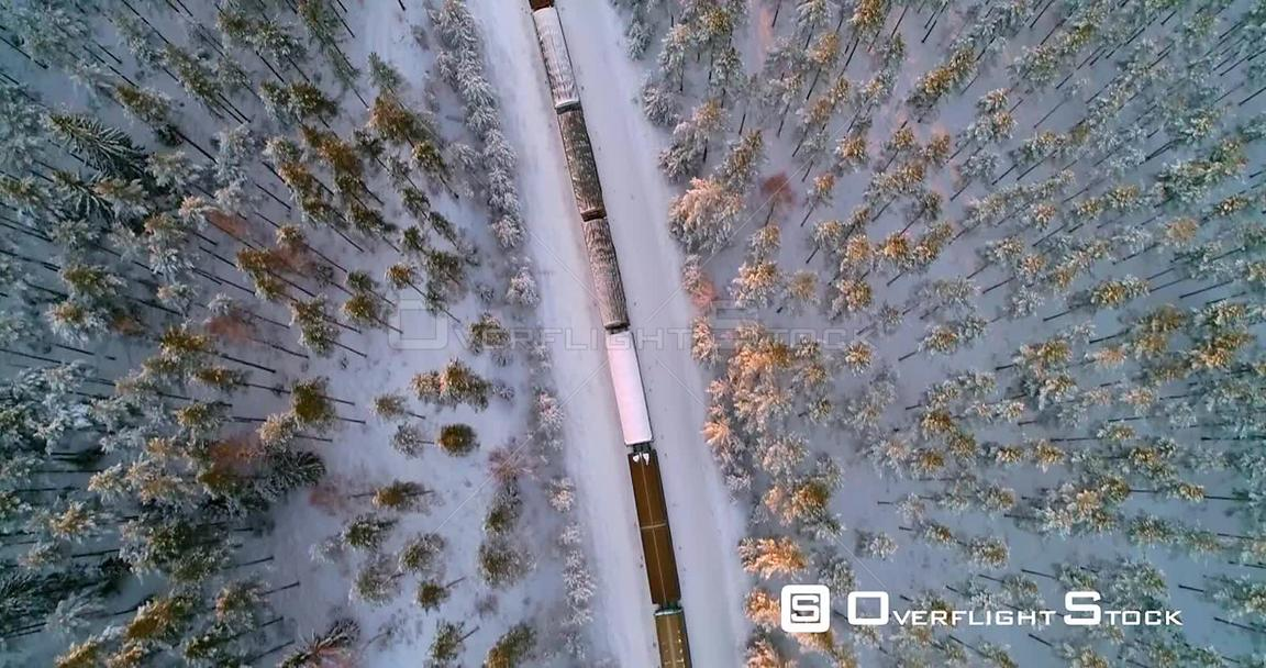 Train in Finnish Winter, Aerial, Top Down, Drone Shot, Following a Cargo Locomotive, in a Snowy Forest, in the Scandinavian Countryside, on a Sunny, Wintry Evening, in Uusimaa, Finland