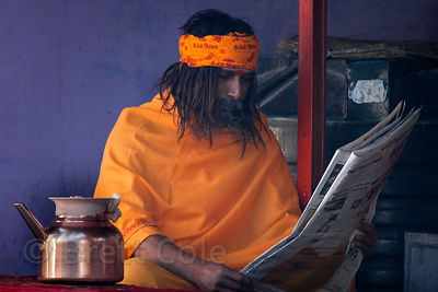 A sadhu (holy man) reading the morning paper, Pushkar, Rajasthan, India