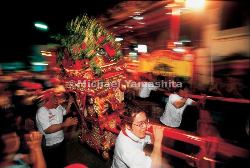 An image of Zheng He is paraded through the streets of Semarang inside a portable shrine, mimicking the movement of a ship over water.