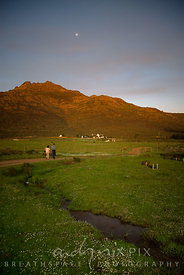 Couple walking along a farm track leading up to house and farm buildings below a mountain, stream in foreground, at sunset