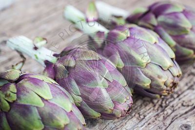 Mallorcan grown baby purple artichoke on rustic wooden board,