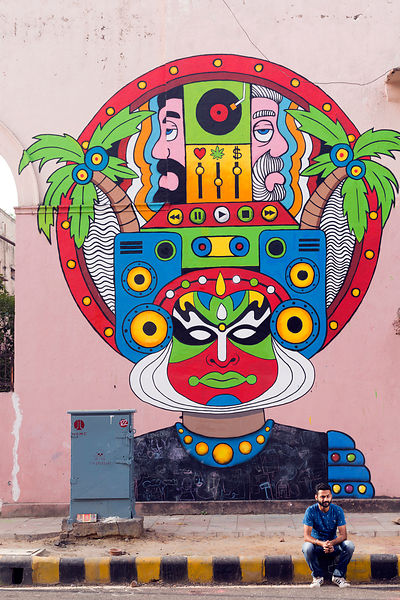 Artist Harsh Raman in front of his piece entitled Katha-Crazy Twins: Chiller Champa & Boom Bhaijaan' on display in the Lodhi Colony area of New Delhi