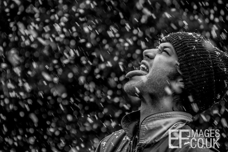 Man Catching Snow Flakes On His Tongue