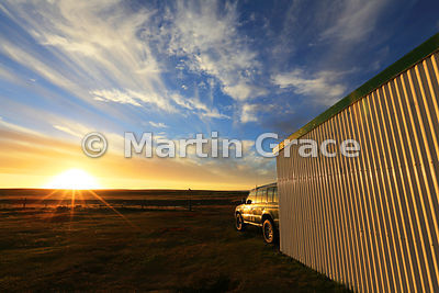 Sea Lion Island sunset with Mitsubishi Shogun and corrugated iron shed, Sea Lion Island, Falkland Islands