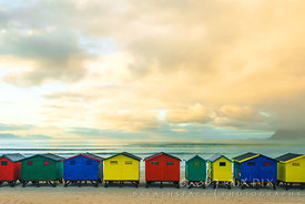 Brightly coloured bathing huts on a beach, calm sea behind reflecting pastel coloured clouds in sky at sunrise.