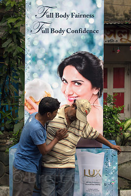 "Two drunk men talk beneath a glamorous sign selling skin whitening products called ""White Impress"" to middle and upper class women, Beniatola, Kolkata, India. Western makeup companies aggressively promote skin whitening and it is an obsession for many in India."