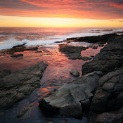 Sunset over rocky coastline