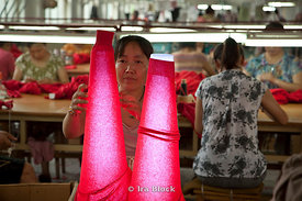 A woman performs her quality control task on the arms of a sweater at a cashmere sweater factory in Qi Shan, China.