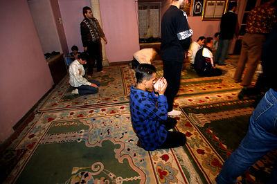 Men pray in the mail mosque in Skanderbeg Sqaure, Tirana, Albania