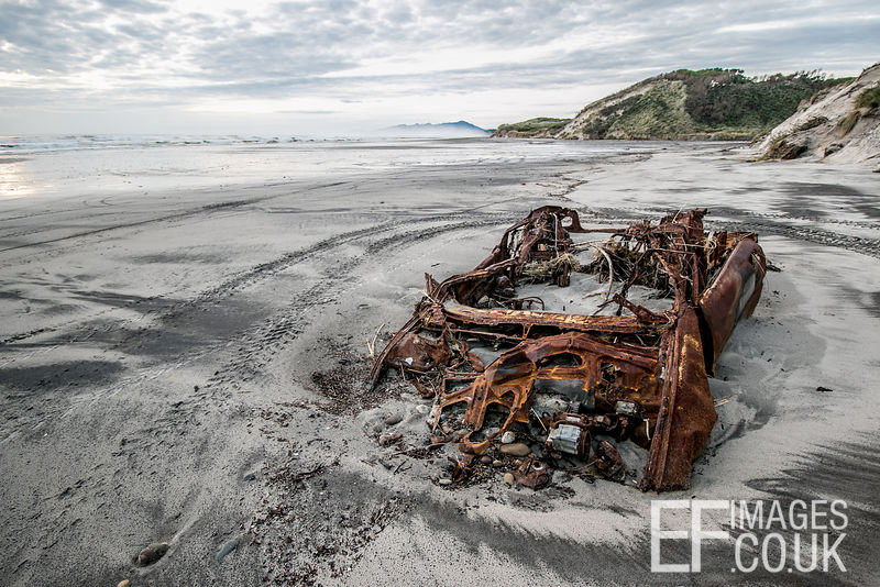 Rusted Out Car Remains On A Beach Near Strahan, Tasmania