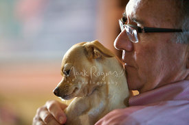 Senior man holding small dog up to his chin
