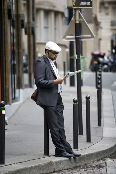 France - Paris - A man reads a newspaper on the Rue Mouffetard.