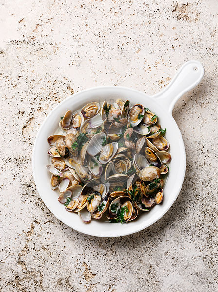 Vongole Shells Clams with parsley in pan on travertine stone background