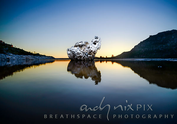 Single large rock reflected in still water at dusk