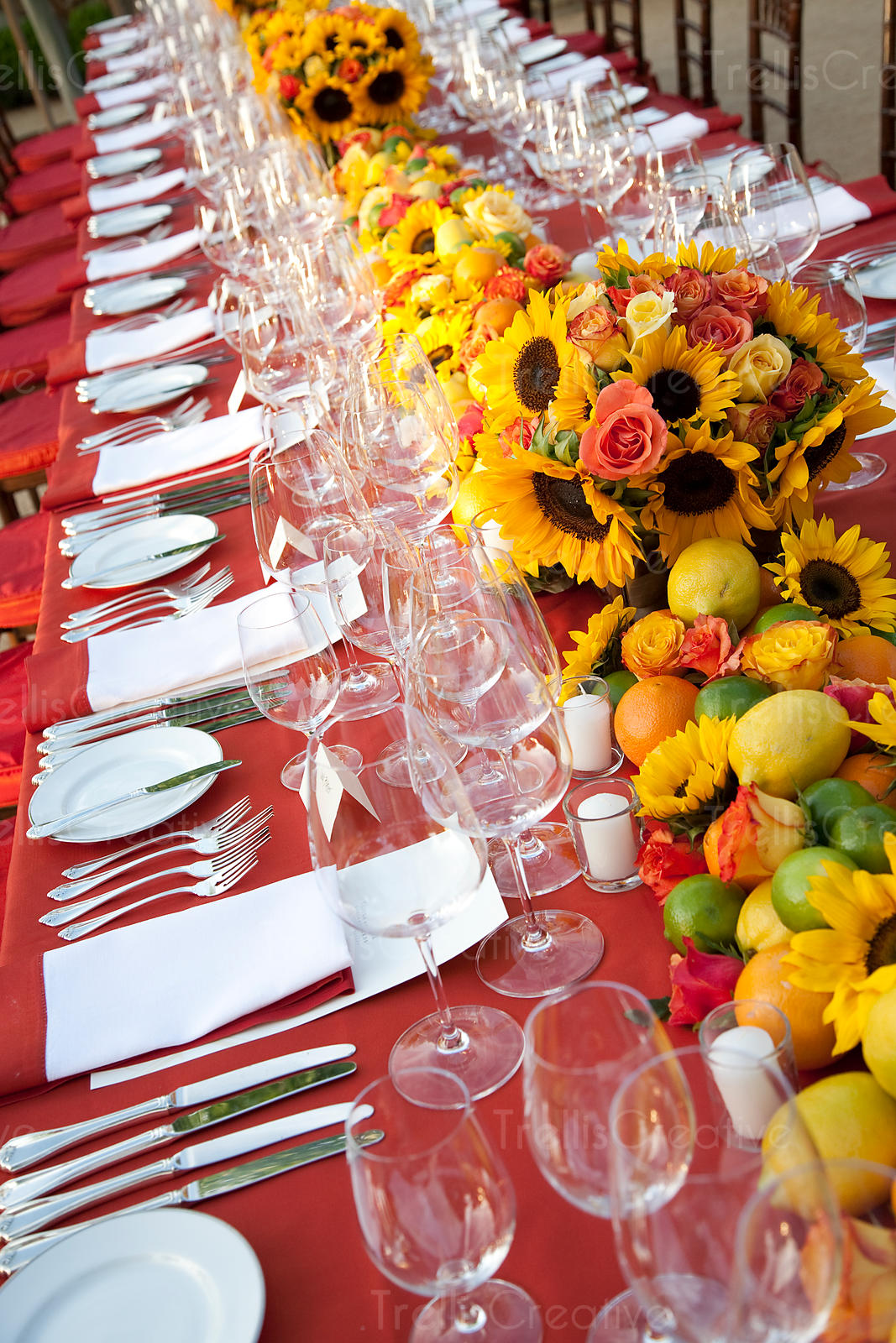 Long table festively decorated with sunflowers and fine china for party