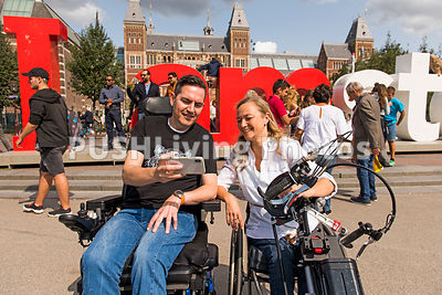 Couple using power wheelchairs talking a selfie in Amsterdam