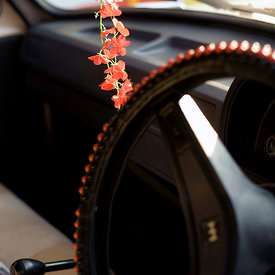A garland of flowers hang from the mirror of an Hindustan Ambassador car, Tamil Nadu, India