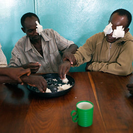 Patients have breakfast before the doctor takes off their bandages after their surgery. Double cataract patient Chansa Lloyd (second right) is helped to eat by others