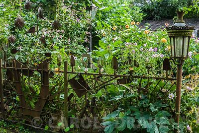 Fence made using old garden tools. The Secret Garden at Serles House, Wimborne, Dorset, UK
