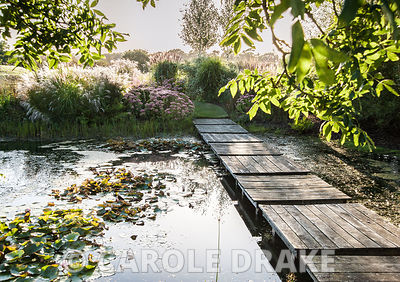 Simple wooden decking creates a pleasing pattern across a large S-shaped pond. The Oast House, Isfield, Sussex, UK