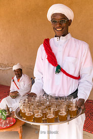 A local offering tea in the Moroccan village of Khamila, founded in the 1950's near Erg Chebbi, Sand dunes area of the Sahara in Morocco
