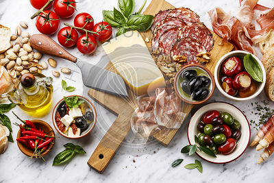 Italian snacks food with Ham, Sliced bread Ciabatta, Olives, Parmesan cheese, Grissini bread sticks, Feta cheese with dried tomatoes and Sausage on white marble background