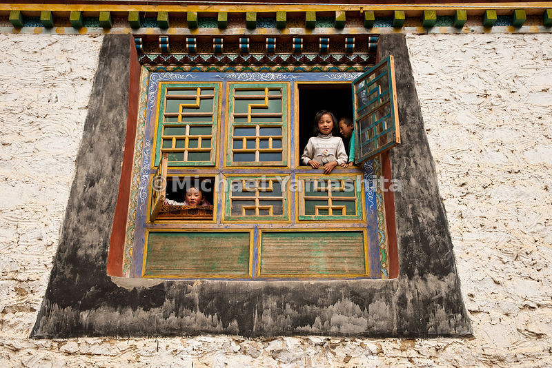 Children peer from intricately decorated windows, framed by traditional Tibetan architecture that is fast disappearing.