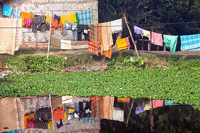 Colorful laundry is reflected in a canal in Chingrihata, East Kolkata Wetlands, Kolkata, India.