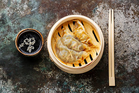 Gyoza dumpling in bamboo steamer, chopsticks and sauce on metal background