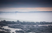 Wiltshire, England - 30th Dec 2014 - Salisbury Cathedral spire in morning mist with frost on downs surrounding Salisbury