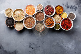 Superfoods and cereals selection in bowls: quinoa, chia, goji berry, mung bean, buckwheat, bean, turmeric, polba, bulgur, lentil, sesame, flax seed, wild rice, almond on grey concrete background copy space