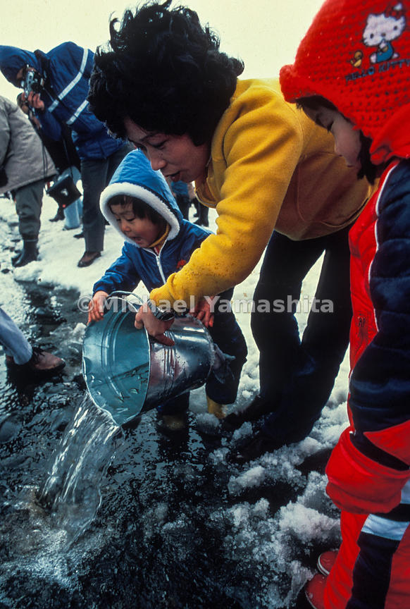 A youngster starts salmon fry on their way to the sea in Sapporo's Salmon Baby Festival, an event that reintroduced the fish to a once polluted river in the city's center.